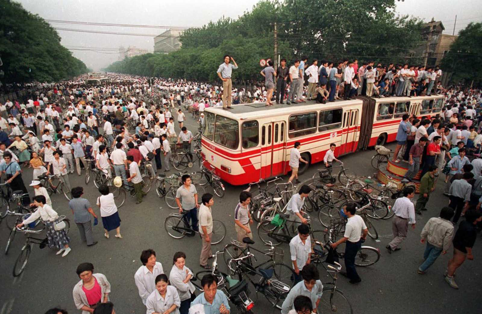 A huge crowd gathers at a Beijing intersection where residents used a bus as a roadblock to keep troops from advancing toward Tiananmen Square in this June 3, 1989 photo.