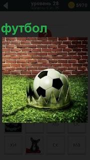 На зеленой траве внутри короны лежит мяч для приготовленный футбола