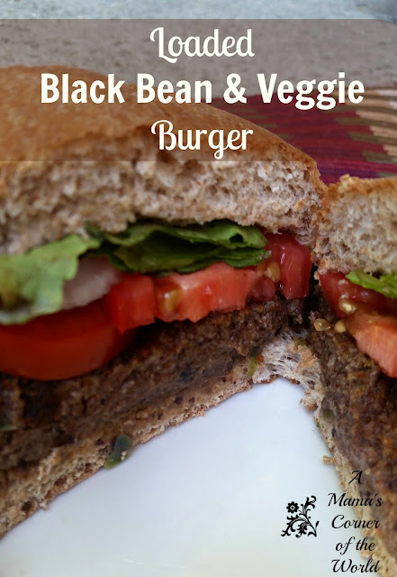Pinnable image of a black bean veggie burger with tomato, lettuce and onion on a bun.