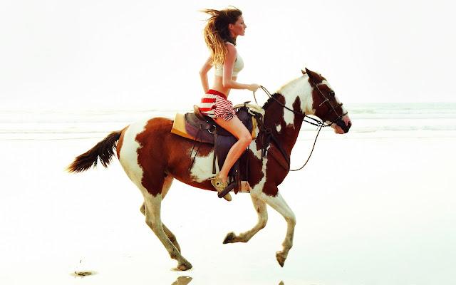 Vrouw rijdend op een bruin wit paard op het strand