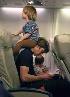 Papá intentando leer en un avión