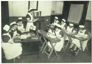 Photograph shows nurses receiving instruction at the Adelaide Hospital, Dublin, Ireland, c. 1950. Five student nurses sit at two rows of desks, facing a senior nurse seated at a larger executive desk with two other nurses at her shoulder. One desk is empty and the former occupant, a student nurse, is apparently reading something aloud to the other nurses.