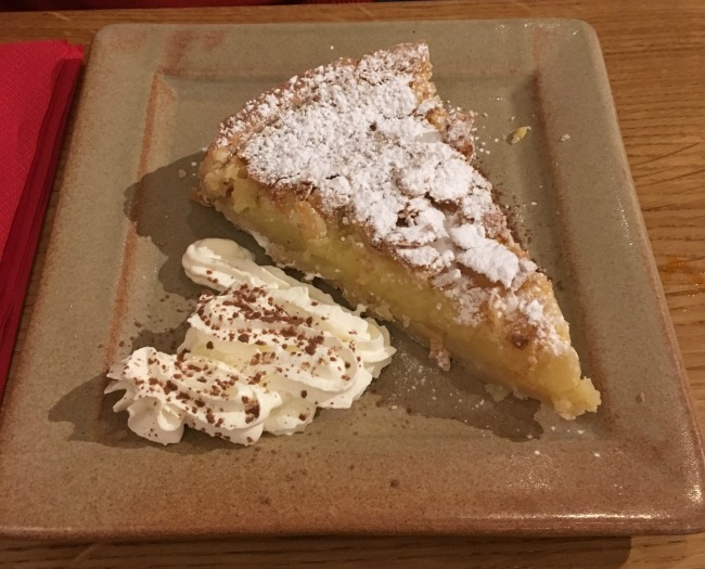 A picture of Almond tart and cream on a square plate