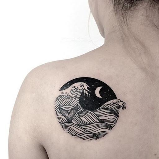 Uma vinheta de uma noite mostra uma paisagem marinha cresting onda com um rabo de baleia fora da água, enquanto uma lua crescente senta-se no fundo.