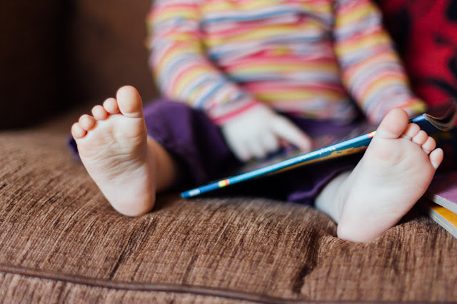 Shot of a child's feet with a book nearby as they sit on a sofa