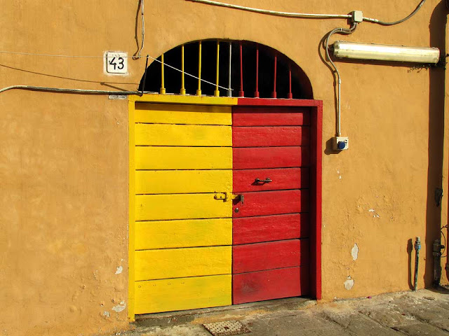 Red and yellow door of a cantina, scali delle Cantine, Livorno
