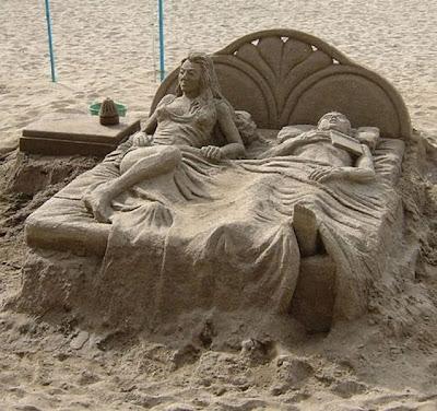 Escultura de arena pareja en la cama