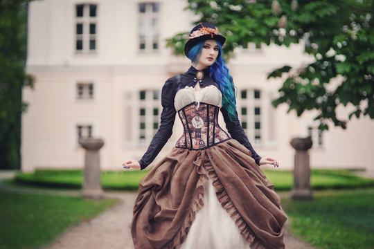 Woman wearing steampunk princess skirt, blouse, bolero jacket/shrug, corset and hat. Ethereal steampunk clothing