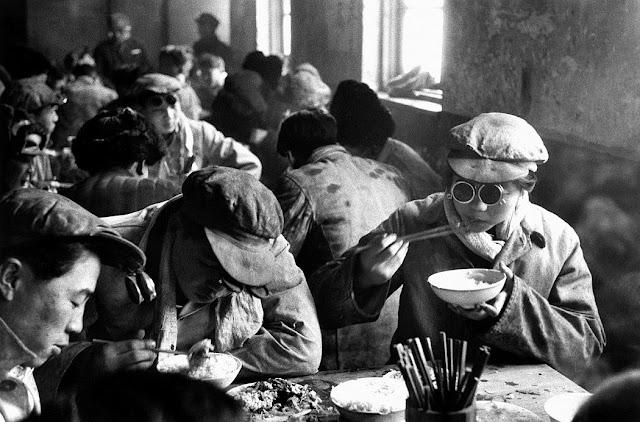 Operai che mangiano nella mensa di una fabbrica cinese. Fotografia di Marc Riboud