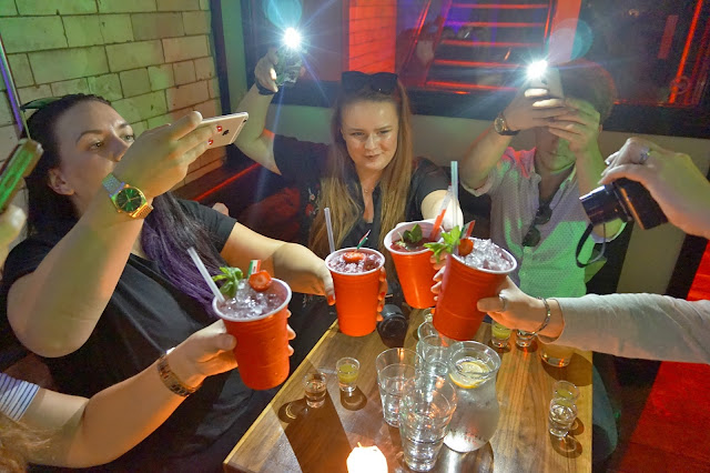 bloggers taking photos of drinks in red cups
