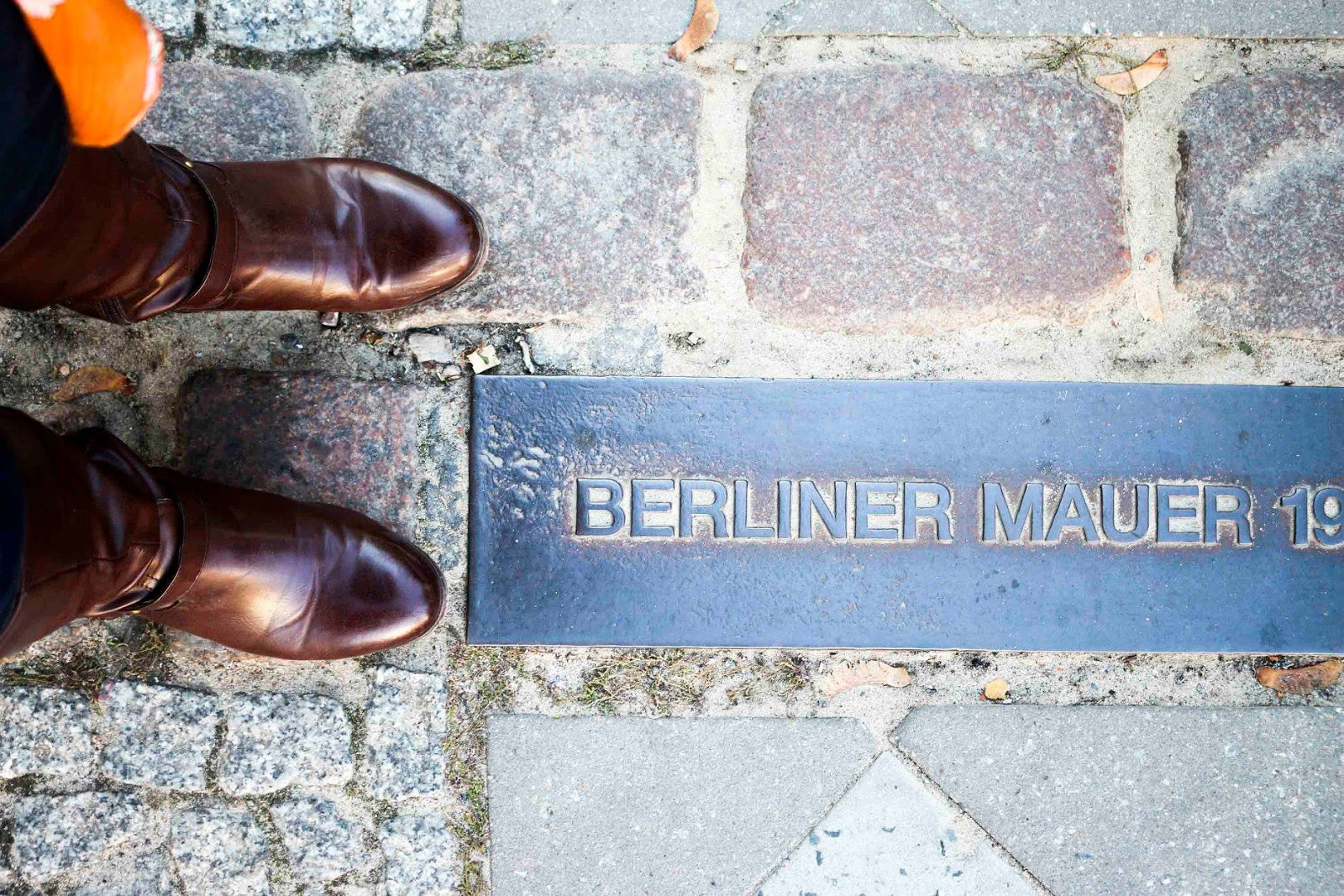Standing over the Berlin wall marker