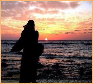 gambar gadis muslimah bertudung labuh di tepi pantai pada waktu senja melihat matahari terbenam