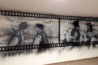 """Artystyczne malowanie ściany w motyw z filmu """"Sami Swoi"""", czarno-biały mural w sali telewizyjnej"""
