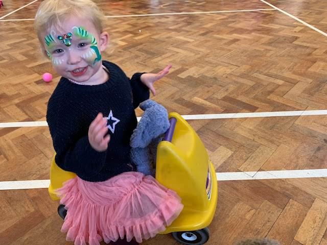 A toddler in party dress, with make up on sitting on a yellow ride on toy and with a blue jelly cat elephant tucked in the seat