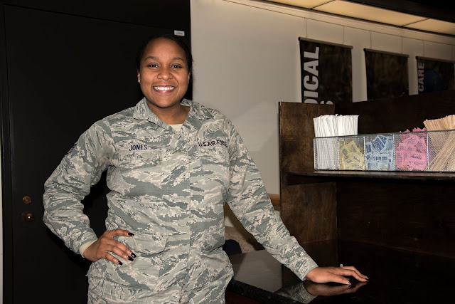 A female in a U.S. Air Force uniform stands in front of the coffee bar while posing for a photo.