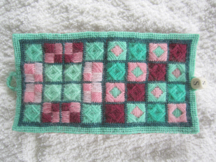 embroidered canvas worked in a variety of filled squares in green, pink and burgundy