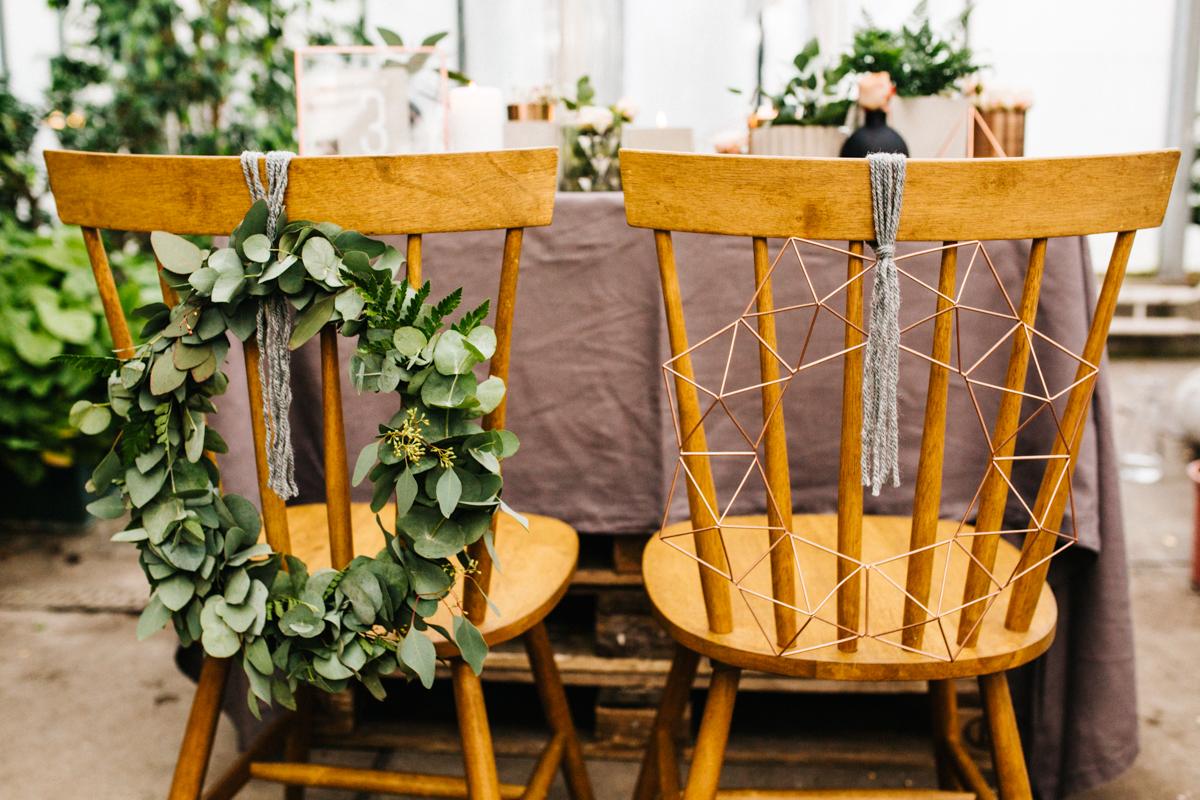 Zielone wianki jako ozdoba krzeseł weselnych