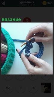 Женские руки осуществляют вязание на спицах, показан рисунок