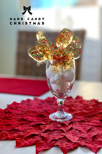 Free-formed hard candy lollipops in a vase, on a white table with a red poinsettia.