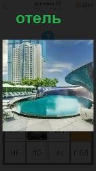 около водоема стоит высокий красивый отель необычной формы