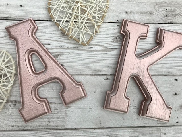 Wooden letters that have been spray painted rose gold next to some small wicker hearts