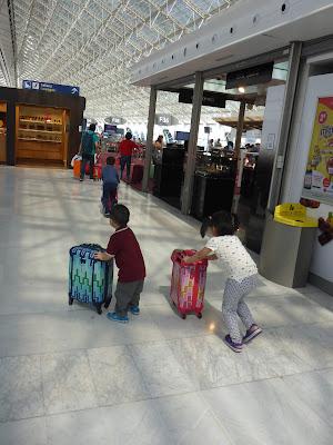Drei Kindergarten- und Grundschulkinder rennen mit Koffern durch die Halle