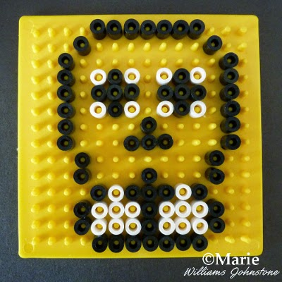 Black and white melty beads making pattern on a yellow board