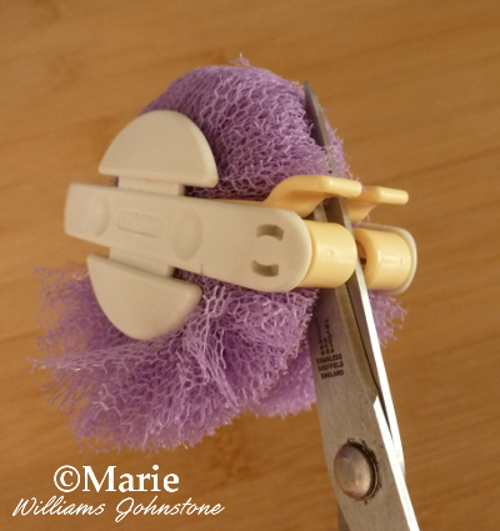 Cut around the middle of the Clover pom pom maker with a very sharp pair of scissors