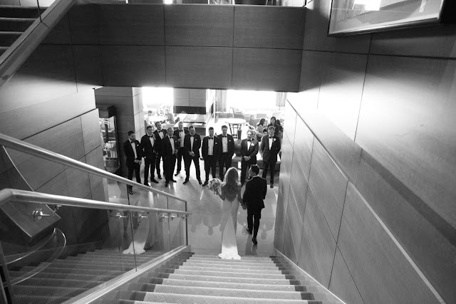 The bridal party greets the couple at the bottom of the stairs | Karen Hill Photography