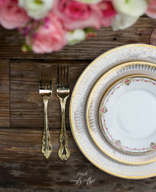 Gold dishes and pink flowers with gold flatware on rustic tabletop with raindrops