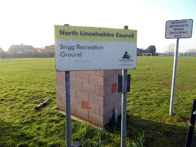 Brigg Recreation Ground's entry sign and one of the football pitches - February 2019
