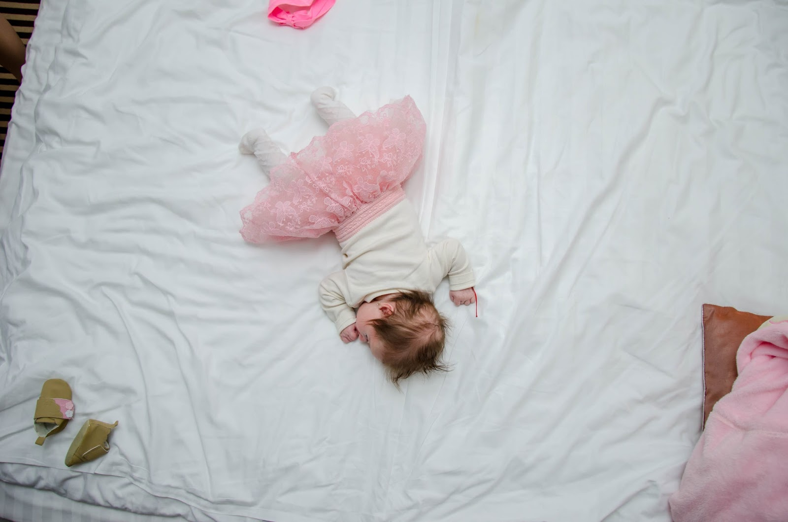 baby in a tutu fast asleep on a bed
