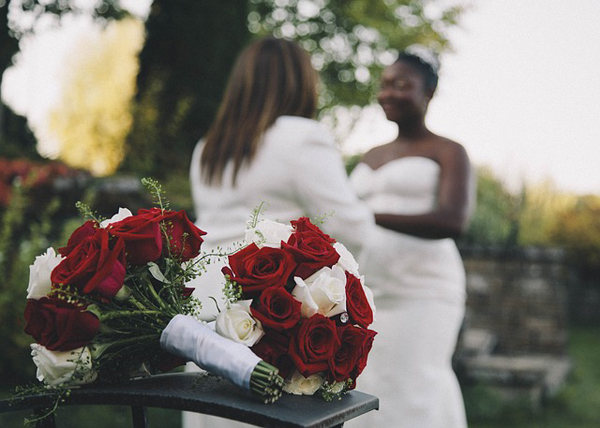 image of two women, one white woman with her back to the camera, and one black woman, facing the camera, getting married; two bouquets of red roses sit in the foreground