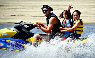 Two boys jet skiing with their camp counselor