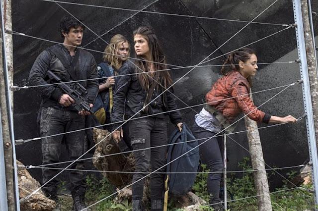 Na foto: Cena de The 100 mostrando Bellamy (armado), Clarke, Octavia e Raven com mochilas desmontando uma cerca pra passar