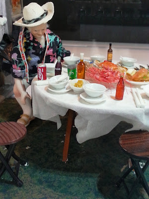 Miniature scene of a person at a table holding various plates of seafood and bottles.