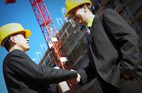 Bir inşaat şantiyesinde el sıkışıp anlaşan baretli müteahhitler