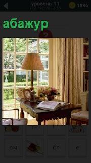 Около окна на столе стоит настольная лампа с абажуром и раскрытая книга на краю с букетом цветов в вазе