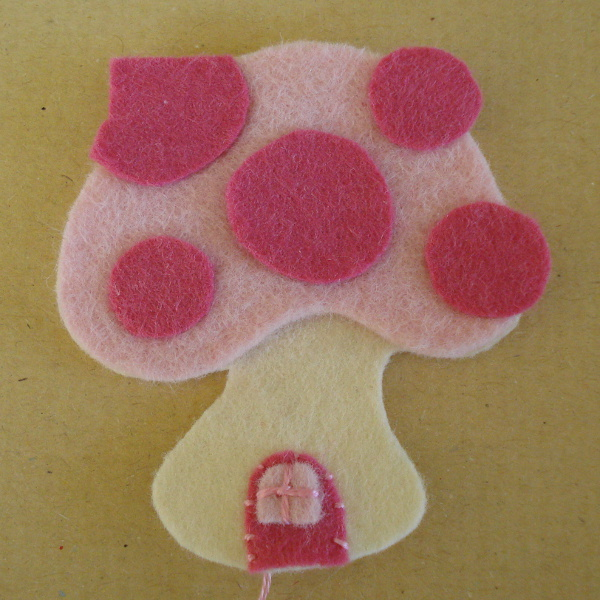 Adding the details for the pink mushroom house felt ornament design