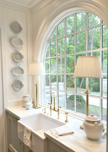 Stunning kitchen with arched window above farm sink and glazed blue plates on wall
