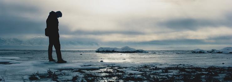 冬の岸辺で俯いている男