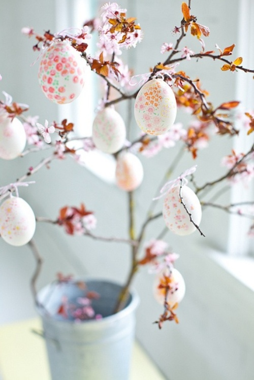 pastel pink Easter decoration with Easter eggs and blossom branches
