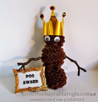 googly eyes and gold crown on knitted poo
