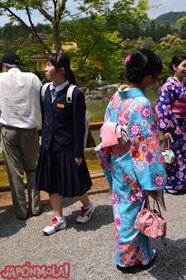 Chica vestida de kimono con el KinkakuJi al fondo