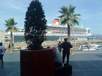 "Two violinists playing their upbeat melodies to cruise passengers ""Queen Mary 2"" docked in Vigo"