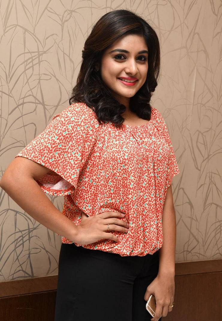 Niveda Thomas Smiling Photos In Orange Dress