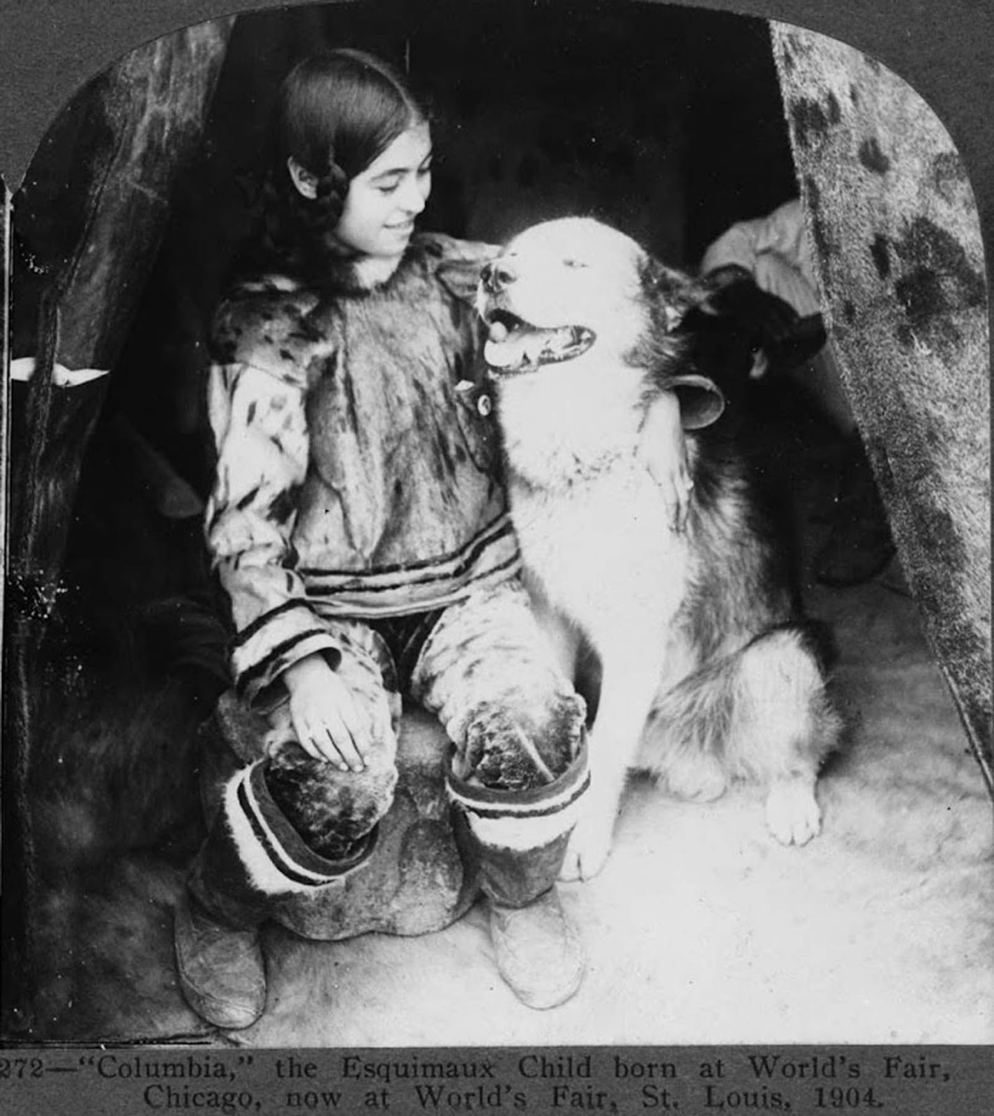 This Eskimo child, pictured with a dog, was born at World's Fair in Chicago and is pictured after being transferred to World's Fair, St. Louis in 1904.