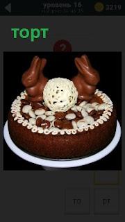 Приготовлен шоколадный торт с зайцами на верху, украшенный белым кремом по периметру