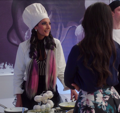 Kamilah, a Pakistani woman, has two enormous dark braids of hair, ending in dyed pink and white strands, and is wearing a chef's hat and a white jacket. Tahani's standing with her back to the camera. At the bottom of the picture, there's a rack of eggs and two frying pans.