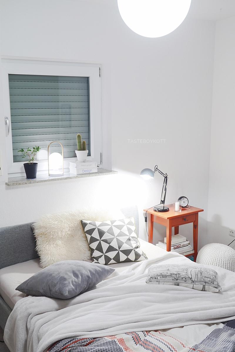 Schlafzimmer gemütlich modern skandinavisch schlicht am Abend einrichten: Tischleuchten, Wohntextilien in weiß + grau, Bildbände